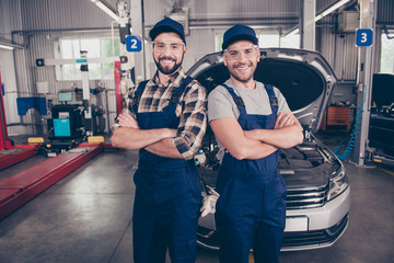 Welcome to our car service. Two experts  with arms crossed, smiling at camera, in special safety outfit and glasses, headwear, standing over background of entrance of automobile in work station Wall mural