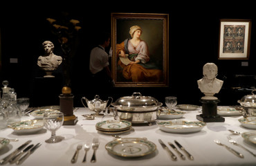 A member of Sotheby's staff poses for a photograph with a  portrait of Emma Hamilton which forms part of the sale of items celebrating Nelson's Legend, including a dinner set called the Matcham desert service, in London