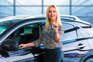 Business woman driver holding auto keys in front of car