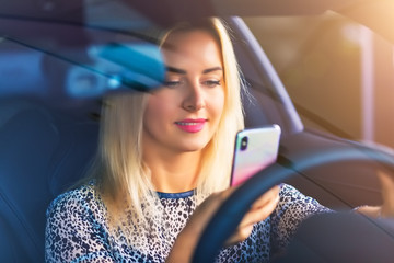 Young woman driver using a smartphone in the car