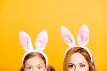 Cropped close up half-faced portrait photo of excited cheerful beautiful mom and small sweet playful funny lovely tender daughter wearing bunny ears isolated on yellow background