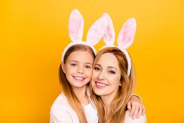 Close up portrait of charming cheerful excited carefree restless gentle tender nice amazing pure mom and small preteen school girl hugging cheek to cheek isolated on yellow background