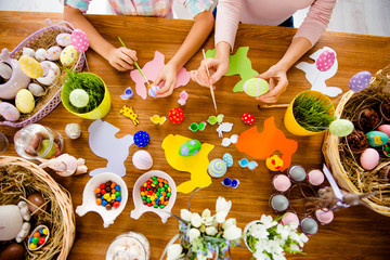 Top view portrait of attractive beautiful colorful easter objects, subjects, things and hand of mother and daughter holding brushes painting small, little eggs, sitting at desk