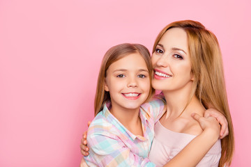 Close up portrait of pretty, charming mother and daughter with beaming smiles over pink background, bonding cheek to cheek, hugging, looking at camera, women's day