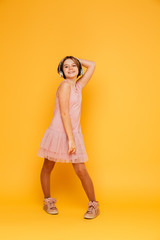 Funny smiling girl in headphones posing isolated over yellow
