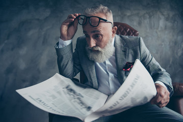 Omg! Attractive, astonished boss in suit take off glasses, shocked, impressed from facts, information in newspaper, sitting in leather chair, money,  shares, stock, gray background