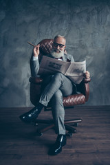 Cheerful, handsome, old, smiling boss in spectacules, suit watch, look, read newspaper, smoke cigarette, sitting in leather chair in workstation, wooden floor, gray background, relax, fun, fashion