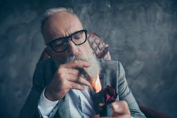 Close up portrait of attractive, ideal, stunning, brutal, harsh, old man, dandy in glasses, tux setting on fire cigar over gray background