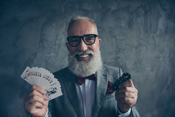 Venturesome, gambling, smiling, lucky old millionaire in glasses hold, show, have, set of cards and five chips, ready for casino, poker, standing over gray background, fun, leisure, winner, win