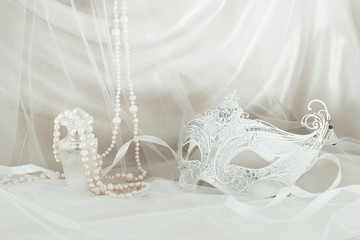 Image of delicate and elegant white venetian mask in front of tulle background.