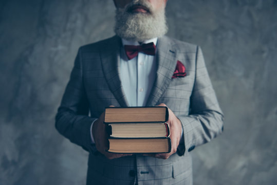 Cropped close up photo of smart serious confident modern stylish trendy teacher dressed in checkered grey jacket with vinous bow-tie handkerchief showing a pile on book isolated on grey background