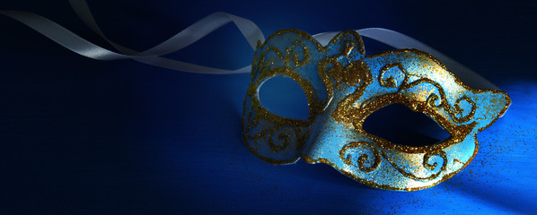 Image of elegant blue and gold venetian, mardi gras mask over blue background. Wall mural