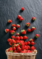 Strawberry explosion. Photo of strawberry in basket on black slate. Top view. High resolution product.