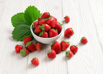 Healthy strawberries in bowl on wooden table. Close up, high resolution product. Harvest Concept