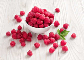 Sweet raspberries in bowl on wooden table. Close up, high resolution product. Harvest Concept