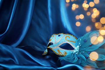 Image of elegant venetian mask over blue silk background.