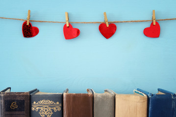 Valentine's day background. Red hearts hanging over rope and old books.