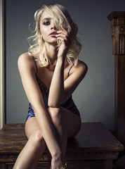 Blonde woman sitting on a bedside table