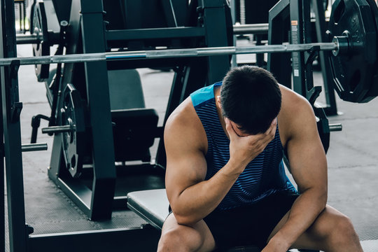 Tired man taking a workout rest. Male athlete suffering a headache or dizziness. Unmotivation in sport and tiredness concept.