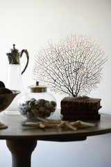 Wooden table and its interior decoration with a gorgon, old books, quail eggs, starfish and a vintage carafe