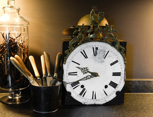 Old clock with silverware and vanilla jar in a black kitchen