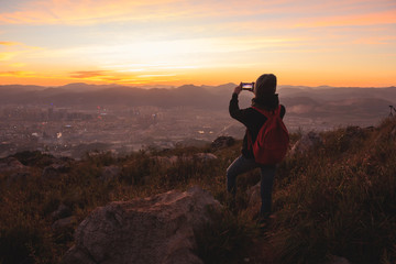 Girl taking pictures of beautiful sunset view with city and mountains