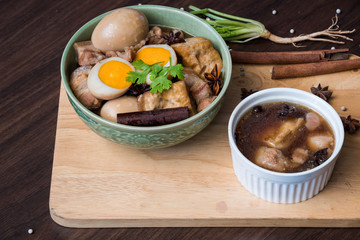Pha-lo : Eggs boiled and pork boiled with spices  and fried tofu in sweet gravy soup on wooden background. Flat lay