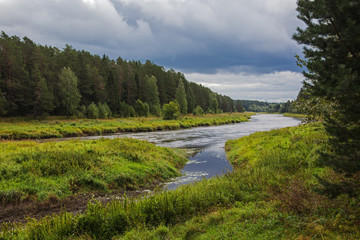 River flowing gently through woodland landscape, view before a thunderstorm. Location in Russia, Tverskaya oblast