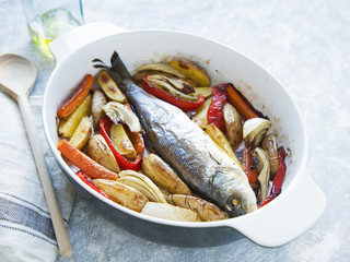 Whole sea fish cooked in casserole dish with vegetables (paprika, carrots, potatoes, fennel) on grey and blue background.
