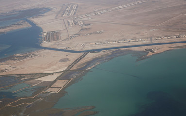 An aerial view of Arabian Gulf with city of Abu Dhabi is pictured through the window of an airplane of Etihad Airways
