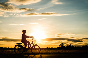 Silhouette woman cycling at sunset