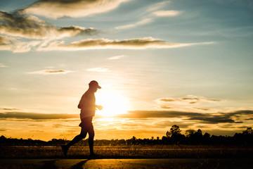Silhouette man running at sunset