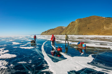 group of tourists with ice sleds walking along the ice of Lake Baikal