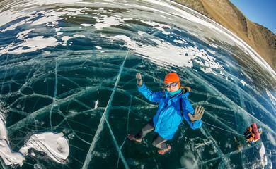 tourist with sleds walks along the blue ice of Lake Baikal.