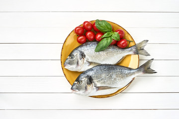 Fresh dorado fish on yellow plate with tomatoes on white wooden table. Top view, copy space.