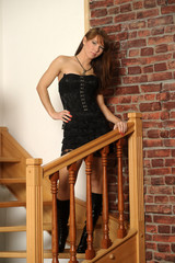 sexy girl in black stands on a wooden staircase