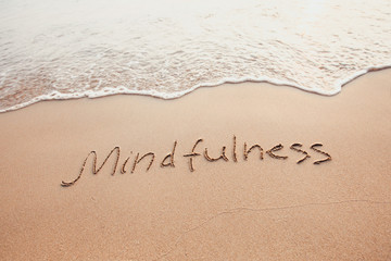 mindfulness concept, mindful living, text written on the sand of beach