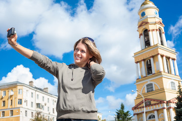 Young joyful woman taking self-portrait photograph with easily handled camera against bell tower of church in Russia