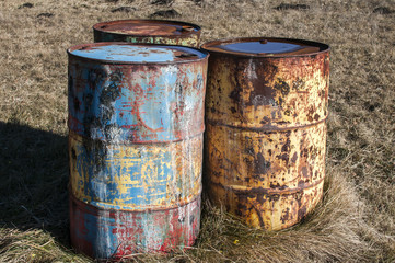 Old rusty abandoned grunge fuel barrel drums in the middle of paintball dry grass field playground