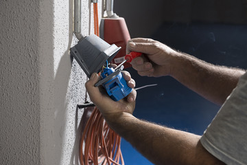 Electrician installing electricity cables.