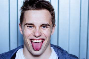 Close up portrait of a young man showing his tongue. Metallic garage door background.