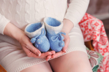 Pregnant woman, pregnancy, motherhood. Waiting for baby. Little baby's bootees in mom's hands