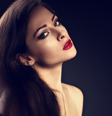Beautiful makeup woman with perfect skin, red sexy lipstick, smokey eye effect make-up and fashionable brows on grey dark background. Closeup contrast toned emotional portrait