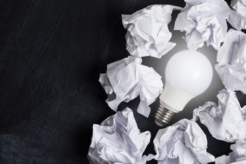 Inspiration and imagination concept. lightbulb with white crumpled paper documents
