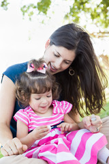 Mixed Race Young Mother and Cute Baby Girl Applying Fingernail Polish in the Park.