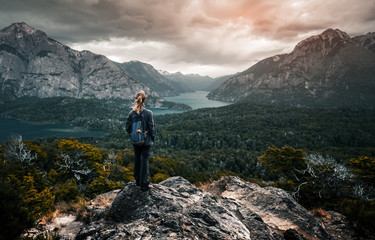 Woman hiker stands and enjoys valley view from viewpoint. Hiker reached top of the mountain and watching sunset. Patagonia, Argentina Wall mural