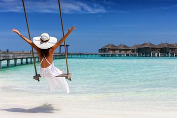 Attraktive Frau im weißen Kleid genießt ihren Sommerurlaub am tropischen Strand der Malediven