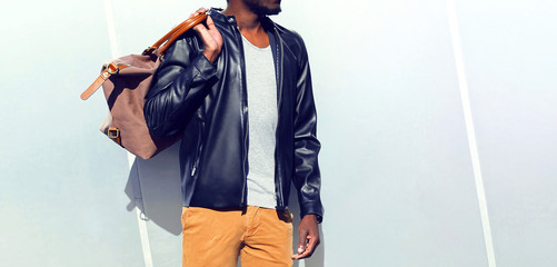 Wall Mural - Fashion african man wearing a black biker leather jacket holds a bag over gray background