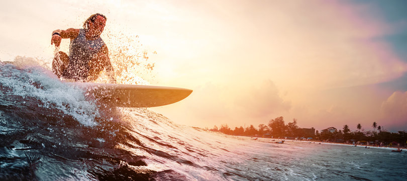 Surfer rides the ocean wave during sunset. Extreme sport and active lifestyle concept