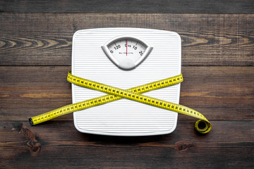 Lose weight concept. Scale and measuring tape on dark wooden background top view